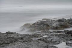 Meereswogen über Felsen bei Cliff Walk in Rhode Island Stockbilder