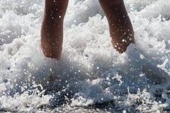 Meereswogen, die über den Füßen des Kindes spritzen Stockfotos