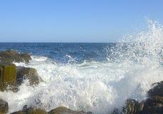 Meereswogen, die über Felsen spritzen Lizenzfreie Stockbilder