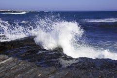 Meereswogen, die auf den Felsen auf dem Ufer zusammenstoßen Stockfotografie