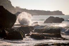 Meereswogen, die auf die Felsen im Sonnenuntergang zusammenstoßen Stockbild