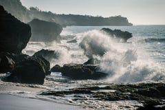 Meereswogen, die auf die Felsen im Sonnenuntergang zusammenstoßen Stockfotografie