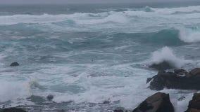Meereswogen, die bei Pebble Beach spritzen stock footage