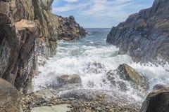 Meereswogen, die gegen ein felsiges Ufer zusammenstoßen Stockbilder