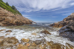 Meereswogen, die gegen ein felsiges Ufer zusammenstoßen Stockfotos