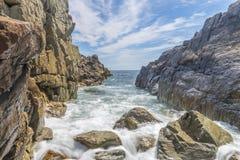 Meereswogen, die gegen ein felsiges Uferlangsames shutterspeed zusammenstoßen Stockfoto