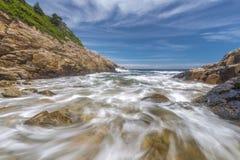 Meereswogen, die gegen ein felsiges Uferlangsames shutterspeed zusammenstoßen Lizenzfreies Stockbild