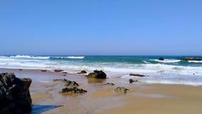 Meereswogen, die gegen Felsen auf sandigem Strand auf Atlantikküste von Portugal zusammenstoßen stock video footage
