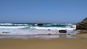 Meereswogen, die gegen Felsen auf sandigem Strand auf Atlantikk?ste von Portugal zusammensto?en stock video footage