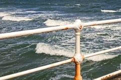 Meereswogen durch verrostende Geländer, Wasserhintergrund mit Kopienraum Lizenzfreie Stockfotos
