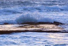 Meereswogen spritzen über ruhigem Felsenregal an der Dämmerung Stockfotos