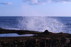 Meereswogen Strandfelsen schlagend Stockbild