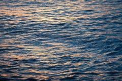 Meereswogen und die Wasseroberfläche bei Sonnenuntergang Stockfotografie