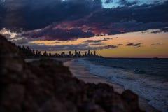 Meereswogen und Stadtbild im Sonnenuntergang stockbild