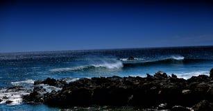Meereswogen vor großer Insel im Mondschein Lizenzfreie Stockbilder