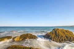Meereswogewimpernansatz-Auswirkungsfelsen auf dem Strand stockbilder