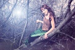 Meerjungfrau sitzt in einem Baum Stockfotografie