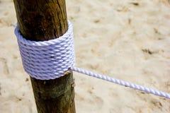 Meertroskabel bij de houten kolom bij het zandige strand stock fotografie