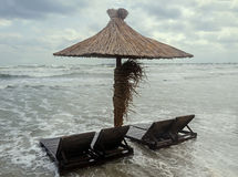 Meerwasser auf Küste mit sunbeds und Strohregenschirm, Sand und blauem Himmel, bewölkter Tag Lizenzfreie Stockfotos