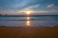 Meerwasser, das auf dem braunen Sandstrand während des Sonnenuntergangs in Phuket Thailand spritzt Stockfoto
