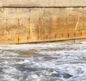 Meerwasser und die alte Betonmauer Stockbilder