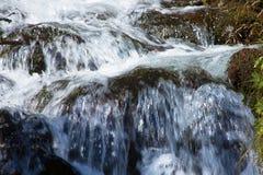 Meeslepend water over stenen Royalty-vrije Stock Foto's