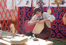 Meester van de productie van Kazakh nationale muzikale instrumenten stock foto's