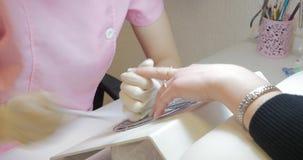 Meester van manicure het indienen de spijkers met een plastic nagelvijl stock video