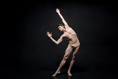 Meesterlijke jonge danser die in de zwarte gekleurde studio presteren royalty-vrije stock foto's