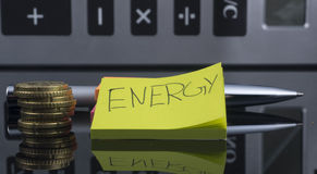 Meet the energy bill. A Pencil with a post ad, money and a calculator in the background Stock Images