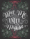 Meet me under the mistletoe hand lettering. Meet me under the mistletoe. Brush calligraphy on blackboard background with chalk. Christmas chalkboard typography royalty free illustration