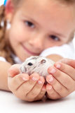 Meet my little pal - girl and her hamster. My little pal - girl holding her hamster in palms Royalty Free Stock Photo