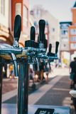 We meet oktoberfest. Hand of bartender pouring a large lager beer in tap. Pouring beer for client. Side view of young bartender po royalty free stock photos