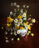A meet of seasons. A still life with flowers and fruits royalty free stock photo