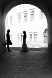 When we meet it smells like magic. Newlywed couple staring one another in a gangway. Black and white image with grain added as effect royalty free stock photography