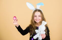 Meet spring holiday. Easter egg hunts as part of festival. Girl little child easter bunny accessory hold dyed egg. Origin of easter bunny. Easter symbols and stock photo
