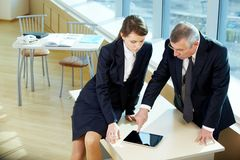 Meeting. Boss pointing at ipad screen during explanation of something to secretary stock photo