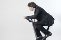 Before meeting. Young businessman riding a fitness bicycle isolated on white background royalty free stock images