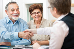Meeting. Senior couple smiling while shaking hand with financial advisor