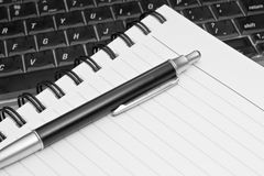 Meeting. Close-up of a notebook and a pen on a semi-transparent laptop keyboard Stock Images