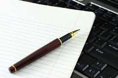 Notebook and pen on computer Royalty Free Stock Photo