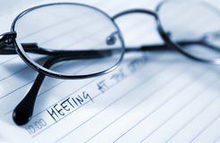 Meeting. A meeting note.Close up of scheduler and glasses Royalty Free Stock Photos