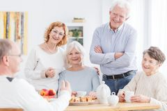 Meeting of active senior club. Members, group of older men and women enjoying tea and sharing their life stories Royalty Free Stock Photo