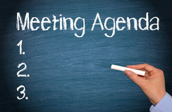 Meeting Agenda - female hand with chalk writing text. And checklist on blue background royalty free stock photo