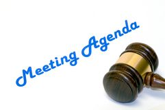 Meeting agenda and gavel. A closeup view of a wooden gavel on a white background with the words Meeting Agenda in blue print Stock Photo