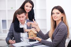 Meeting with agent in office, buying renting apartment or house,. Buyers of real estate ready to conclude a deal, family couple shaking hands with realtor after Royalty Free Stock Image