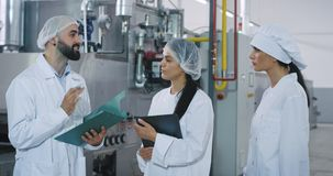 Meeting on the bakery industry factory engineer man with a beard explaining to the bakery workers how to using the. Industrial machine all they wearing stock footage
