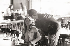 Meeting at the bar. Beautiful smiling women and stylish men meeting at the bar, he is touching her back Stock Photography