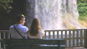 Meeting on the bench near waterfall stock video