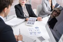 Meeting of Business Analysts. High angle of business people discussing statistics report looking at charts and graphs with financial data during meeting in stock photography